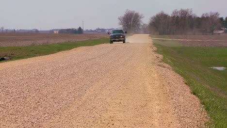 A-pickup-truck-drives-on-a-dirt-road-through-Midwest-farmland