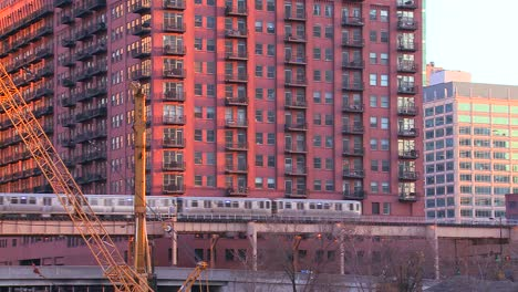 The-El-train-travels-over-a-bridge-in-front-of-the-Chicago-skyline-and-apartments