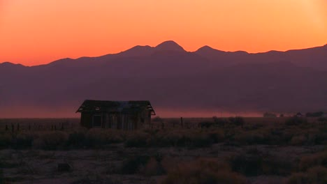The-sun-sets-behind-an-abandoned-cabin-the-desert