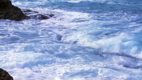 The-camera-tilts-up-from-pounding-ocean-waves-to-reveal-a-fisherman-standing-by-the-sea