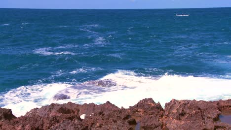Wide-shot-of-waves-breaking-on-the-shoreline-with-a-small-fishing-boat-distant