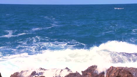 Wide-shot-of-waves-breaking-on-the-shoreline-with-a-small-fishing-boat-distant-1