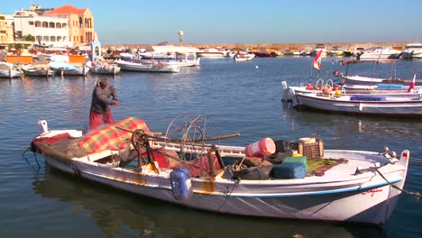 A-traditional-fisherman-works-on-his-net-in-a-harbor-in-Tyre-Lebanon-1