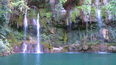 Ein-üppiger-Und-Fruchtbarer-Tropischer-Wasserfall-Fließt-In-Einen-Grünen-Pool-Green