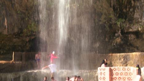 People-bathe-under-a-large-waterfall-of-hot-water-at-a-Dead-Sea-resort-in-Jordan-1