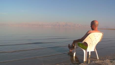 Un-Hombre-Sentado-En-Una-Silla-De-Plástico-Junto-Al-Mar-Muerto-En-Israel