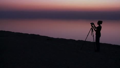 A-woman-photographer-takes-pictures-in-a-purple-golden-glow-after-sunset-behind-the-Dead-Sea-in-Jordan
