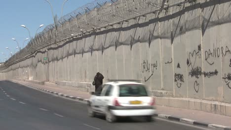 A-Muslim-woman-walks-along-the-new-West-Bank-Barrier-between-Israel-and-the-Palestinian-territories