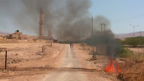 A-fire-burns-on-a-lonely-road-near-a-mosque-in-the-Palestinian-Territories-1