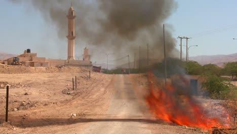 Un-Incendio-Arde-En-Una-Carretera-Solitaria-Cerca-De-Una-Mezquita-En-Los-Territorios-Palestinos-2-Un-Incendio-Arde-En-Una-Carretera-Solitaria-Cerca-De-Una-Mezquita-En-Los-Territorios-Palestinos-2