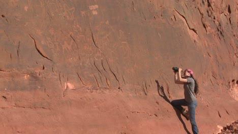 A-woman-photographs-ancient-and-mysterious-petroglyphs-depict-humans-and-camels-in-the-Saudi-desert-near-Wadi-Rum-Jordan