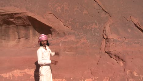 A-traditional-Bedouin-points-out-ancient-and-mysterious-petroglyphs-depict-humans-and-camels-in-the-Saudi-desert-near-Wadi-Rum-Jordan