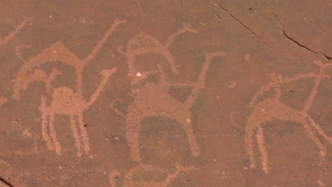 Close-up-of-ancient-and-mysterious-petroglyphs-depicting-humans-and-camels-in-the-Saudi-desert-near-Wadi-Rum-Jordan