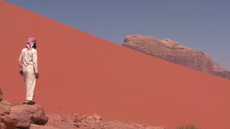 An-Arab-man-walks-to-an-overlook-in-the-Saudi-desert-of-Wadi-Rum-Jordan