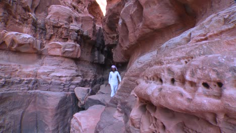 An-Arab-man-walks-along-a-narrow-ledge-in-a-canyon-in-the-Saudi-desert-of-Wadi-Rum-Jordan