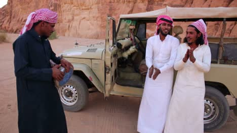 Three-Bedouin-men-sing-songs-near-their-jeep-in-the-Saudi-desert-of-Wadi-Rum-Jordan