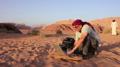 A-man-works-on-a-laptop-computer-in-the-middle-of-the-desert