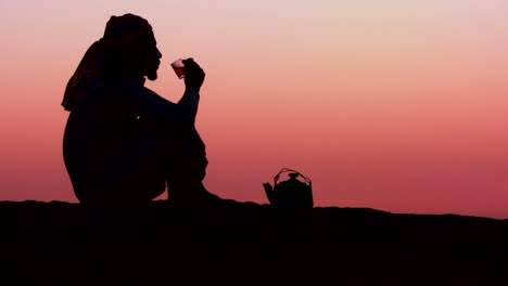 A-Bedouin-man-pours-tea-in-silhouette-against-the-sunset