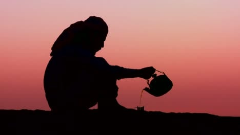 A-Bedouin-man-pours-tea-in-silhouette-against-the-sunset-2