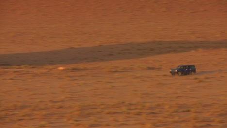 Zoom-Hacia-Atrás-Para-Revelar-Un-Camión-Beduino-Conduciendo-Rápido-A-Través-De-Las-Vastas-Arenas-Del-Desierto-De-Wadi-Rum-Jordan
