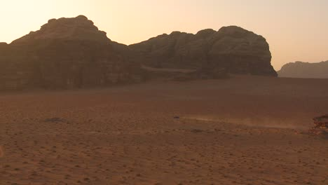 A-trail-of-dust-follows-a-vehicle-across-the-desert-in-Wadi-Rum-Jordan
