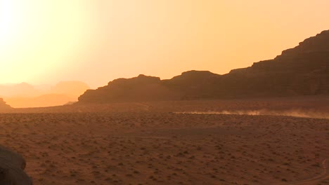 A-trail-of-dust-follows-a-vehicle-into-the-sunset-across-the-desert-in-Wadi-Rum-Jordan