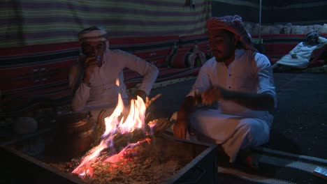 Two-Bedouin-men-sit-in-a-tent-in-front-of-a-campfire-in-the-desert-and-laugh-and-talk