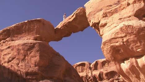 Una-Increíble-Formación-De-Arco-En-El-Desierto-De-Sadi-En-Wadi-Rum-Jordan-Con-Un-Hombre-Beduino-Caminando