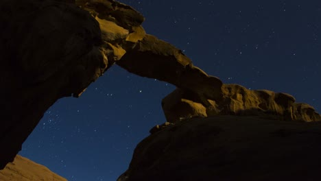 An-incredible-time-lapse-shot-looking-up-at-an-arch-formation-in-the-desert-against-a-night-sky