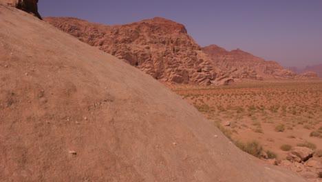 La-Cámara-Se-Mueve-Más-Allá-De-Una-Formación-De-Arenisca-Para-Revelar-El-Vasto-Desierto-Saudí-De-Wadi-Rum