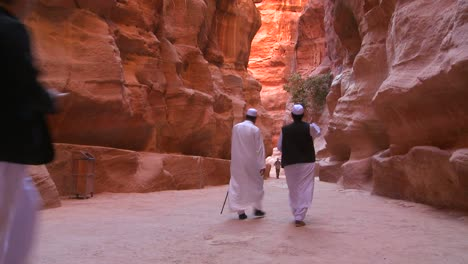 Arab-men-walk-through-the-narrow-canyons-leading-up-to-Petra-Jordan