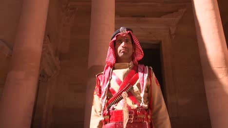Tilt-down-to-Bedouin-warrior-standing-in-front-of-the-facade-of-the-Treasury-building-in-the-ancient-Nabatean-ruins-of-Petra-Jordan