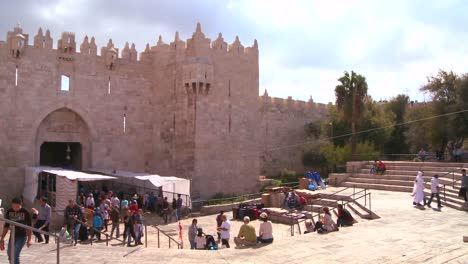 Pan-across-of-people-walk-out-of-the-Damascus-Gate-in-the-old-city-of-Jerusalem-