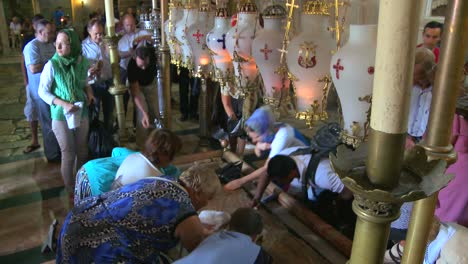 Christian-pilgrims-kneel-and-kiss-the-stone-where-Jesus-was-taken-from-the-cross-in-the-Holy-Sepulcher-in-Jerusalem-Israel