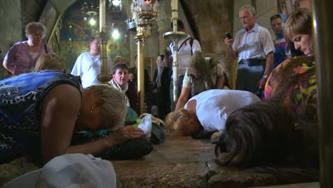 Christian-pilgrims-kneel-and-kiss-the-stone-where-Jesus-was-taken-from-the-cross-in-the-Holy-Sepulcher-in-Jerusalem-Israel-1