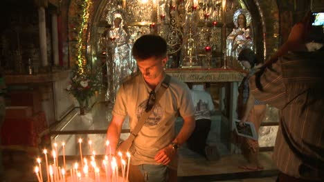A-young-boy-lights-a-candle-in-the-Holy-Sepulcher-in-Jerusalem-Israel