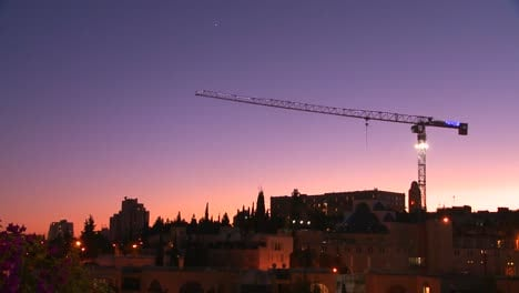 A-construction-crane-towers-in-front-of-the-old-city-walls-of-Jerusalem-Israel-by-night