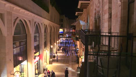 People-walk-through-a-modern-shopping-center-in-front-of-the-old-city-walls-of-Jerusalem-Israel-by-night