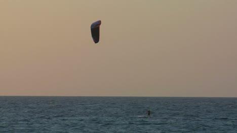 A-windsurfer-moves-along-a-coastline-at-dusk