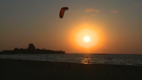 A-windsurfer-moves-along-a-coastline-at-sunset