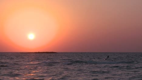 A-windsurfer-moves-along-a-coastline-at-sunset-2