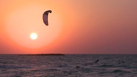 A-windsurfer-moves-along-a-coastline-at-sunset-3