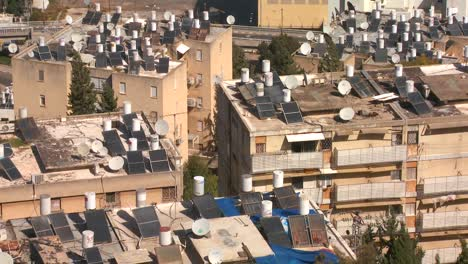 Establishing-shot-overlooking-apartments-and-buildings-in-Haifa-Israel-with-solar-panels-and-water-heaters-on-rooftops