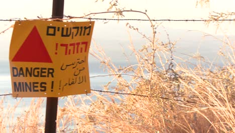 Pan-across-to-a-sign-warning-in-English-Arabic-and-Hebrew-that-mines-are-nearby-along-the-Israel-border-with-Syria