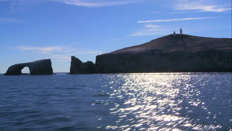 Wide-shot-of-Anacapa-Island-with-its-lighthouse-and-iconic-natural-bridge-visible-as-seen-from-an-approaching-boat