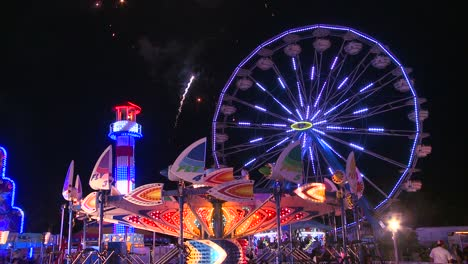 Fireworks-explode-in-the-night-sky-behind-a-ferris-wheel-at-a-carnival-or-state-fair