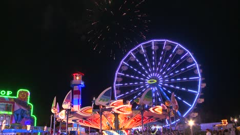 Fireworks-explode-in-the-night-sky-behind-a-ferris-wheel-at-a-carnival-or-state-fair-1