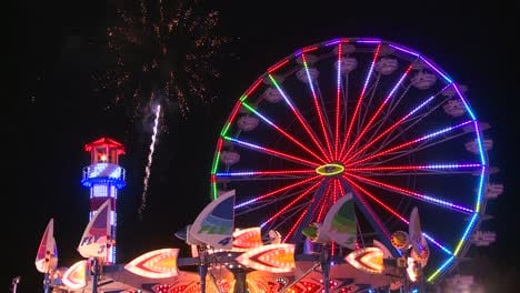Fireworks-explode-in-the-night-sky-behind-a-ferris-wheel-at-a-carnival-or-state-fair-2
