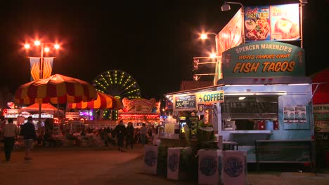 Establishing-shot-of-an-amusement-park-carnival-or-state-fair-at-night-