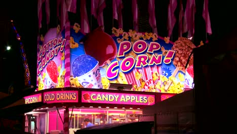 Establishing-shot-of-a-food-stall-offering-popcorn-and-candy-apples-at-an-amusement-park-carnival-or-state-fair-at-night-